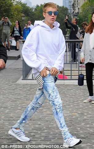 Eye-catching: Heavily distressed acid wash jeans and white Adidas trainers…