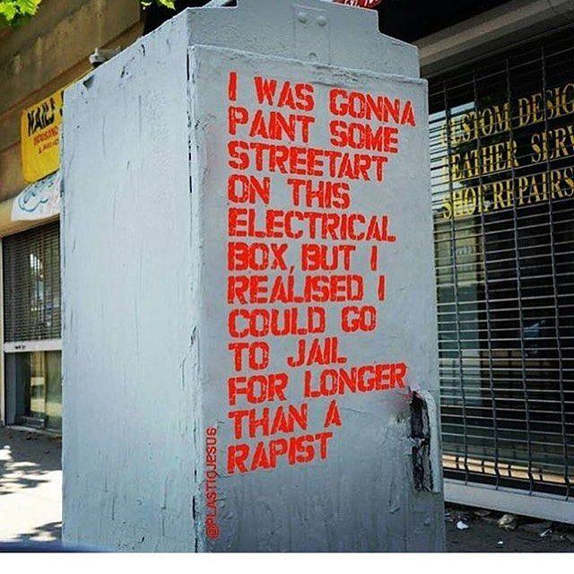 Red powerful street art message rapist v vandalism