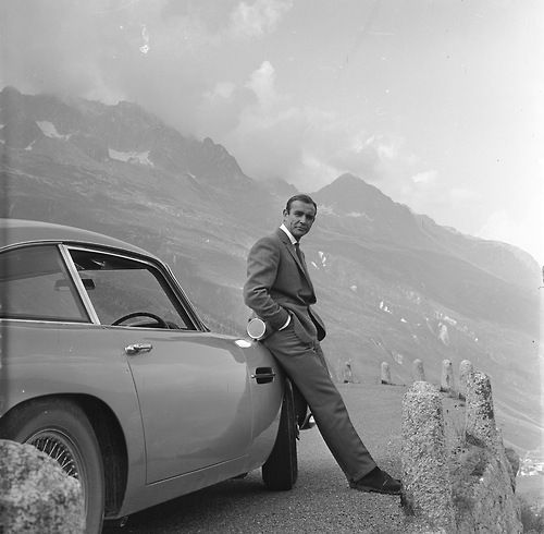 Sean Connery relaxes on the bumper of his Aston Martin DB5 during the filming of location scenes for 'Goldfinger' in the Swiss Alps, 1964. S)