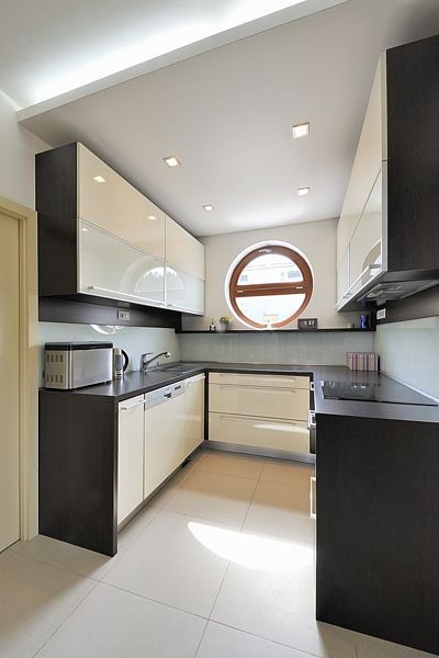 Kuchyňskou linku navrhli architekti z lakovaných MDF desek – světlý lak v kombinaci s laminem v odstínu wengé, obložení pracovní plochy tvoří sklo Lacobel osazené v lištách. Kruhové okénko připomíná rodinnou zálibu v plachtění.