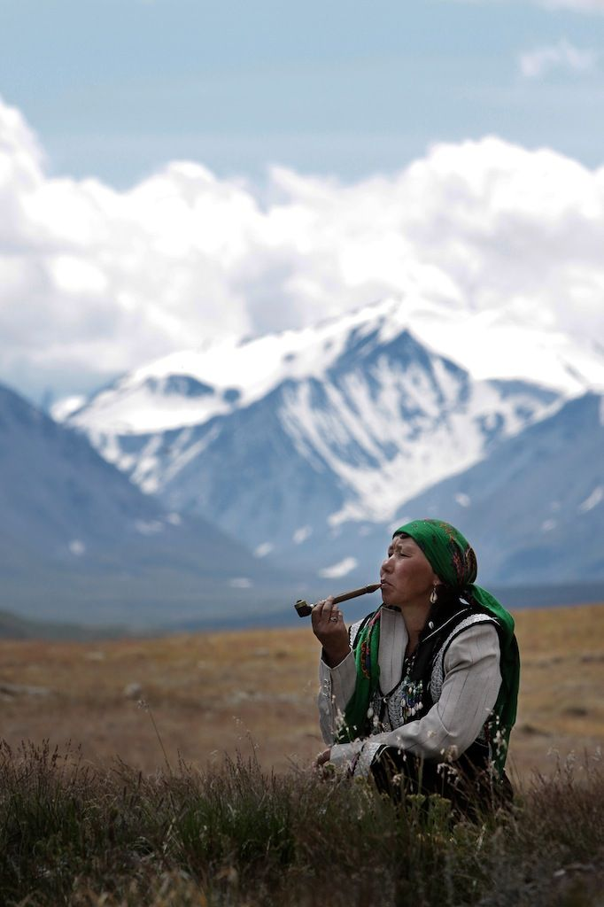 Maria Amanchina, a traditional Altai shaman and healer, lights a pipe as she sends her prayers with the smoke to the Sky, the Land, and the Spirit of Altai.