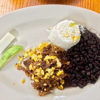 Photo of El Rinconcito Cafe - Washington, DC, United States. Shredded beef with eggs, black beans, rice pilau, avocado, and Salvadoran cheese!