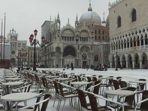 It is St. Mark's, the cafe is ready for customers -- but snow is on the square. No pigeons, no people.