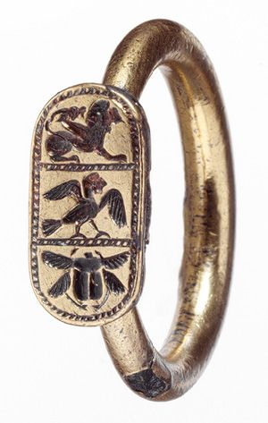 """Ring, late 6th–early 5th century b.c., Etruscan, Gilt silver  """"This ring testifies to the complexity of artistic interconnection at the end of the Archaic period. The bezel is in the form of a cartouche, a shape ultimately of Egyptian origin that the Phoenicians disseminated in the western Mediterranean. The three mythological creatures that decorate it—winged lion, siren, and scarab beetle—came from the East as well."""""""