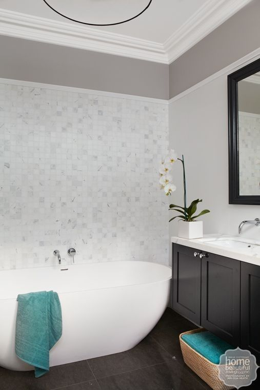 A mosaic wall of white and grey lends a subtle shimmer to this bathroom and contrasts with matt black cabinetry.