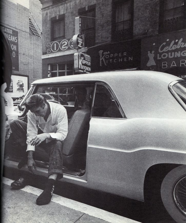 Elvis sitting in his Continental Mark II, putting on his shoes after a long ride from Jacksonville to New Orleans. August 12, 1956.