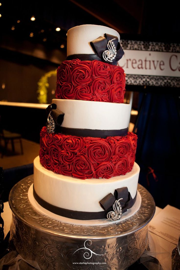 Rosette Wedding Cake - Iced in buttercream, with red buttercream rosettes.  Bows and bands are made of fondant.  Photo curtesy of Starla Photography, www.starlaphotography.com