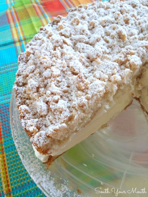 Lemon Crumble Cream Cake with a crumb topping dusted with powdered sugar, tender cake and lemon cream filling.
