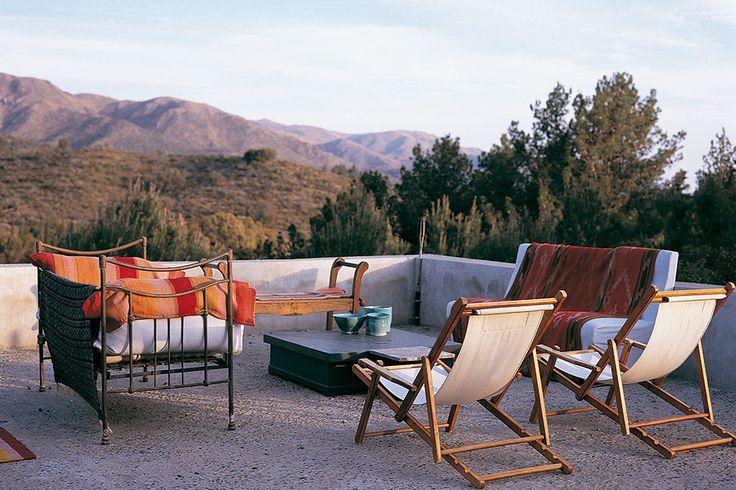 Terraza de una casa en Córdoba con sillones y camastros, abrigados con mantas de telar. Además, reposeras, mesa ratona y banco de madera.