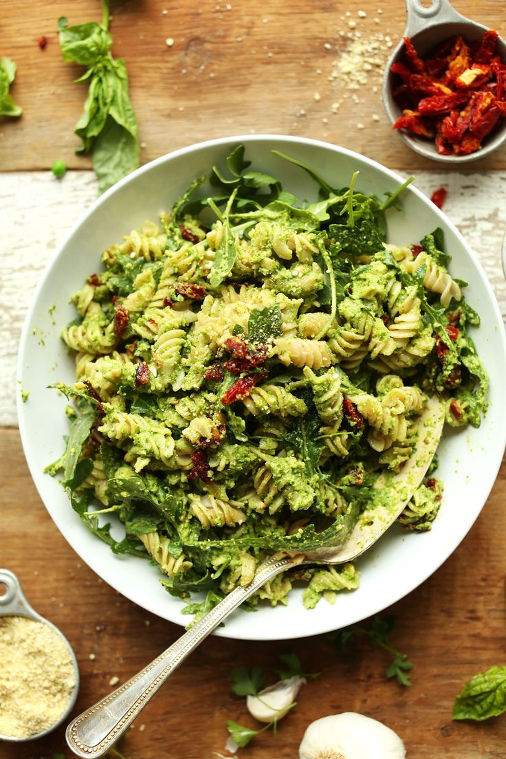 Amazing and quick pea pesto pasta that's vegan, gluten free, and tossed with arugula and sun-dried tomatoes!