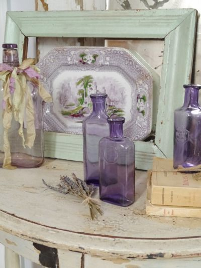 rustic shabby... the colored frame in front of the platter, and purple bottles create a quaint vignette