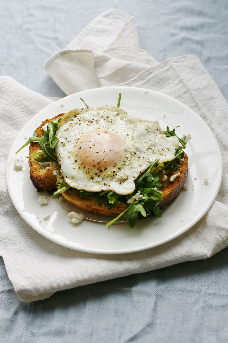 Crispy fried egg on artisan toast with arugula, feta cheese, and herb oil