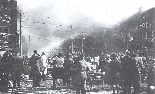Hieronder niet meer: de foto werd gemaakt op 31 maart 1943 na het bombardement om 14:45 uur aan de westkant. De Schiedamseweg staat aan beide zijden in brand en huizen storten in. Op de voorgrond het Marconiplein met inderhaast geredde huisraad. Dit bombardement door Amerikaanse bommenwerpers, dat uiteraard voor de havens was bedoeld en niet voor deze dichtbevolkte woonwijk, heeft grote delen van Bospolder en vooral Tussendijken volledig in de as gelegd