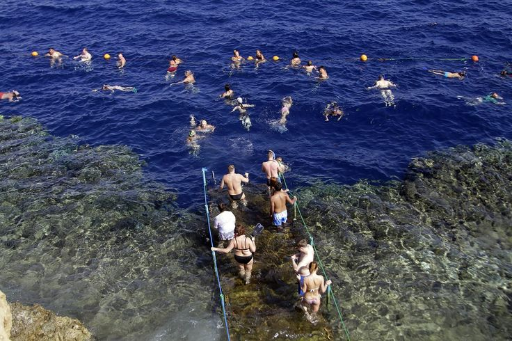 European tourists swim in the Red Sea at a hotel hosting travelers waiting to be evacuated from the resort following the discontinuation of commercial flights between the country and several western European governments, Sharm el-Sheikh, Egypt, 2015, photograph by Ahmed Abd El-Latif.