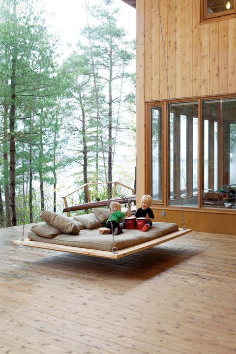 """This Georgian Bay home shared by two families was an architectural experiment in communal living. Two-year-old Annika and five-year-old Soren make music on the """"nap swing,"""" a popular hangout spot for kids and adults alike. View 13 more photos of the home here.  Photo by Lorne Bridgman.   This originally appeared in Communal Lakeside Vacation House in Ontario."""