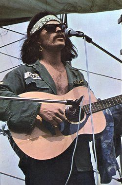 """Woodstock - Country Joe on stage for the """"Fixin' to Die"""" performance."""