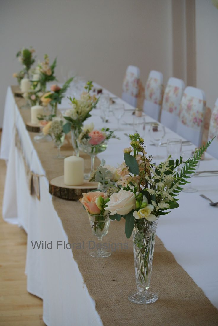 Stokeinteignhead village hall wedding Devon. Chair covers, sashes, hessian table runners and floral designs supplied by Wild Floral Designs. Top table flowers.