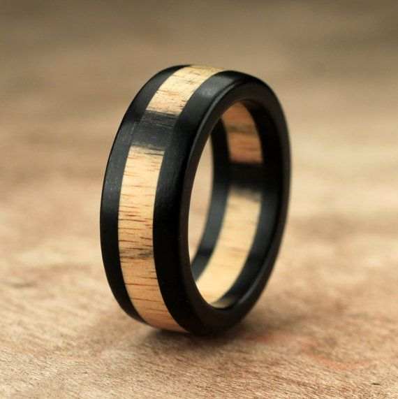 This is a hand carved Ebony and Pale Moon wood layered ring. 46.54