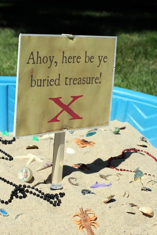 buried treasure activity for pirate themed party in baby pool-- that's a great idea, as long as it's not too hot out, maybe put it in the shade? No need for a pinata or treat bags...