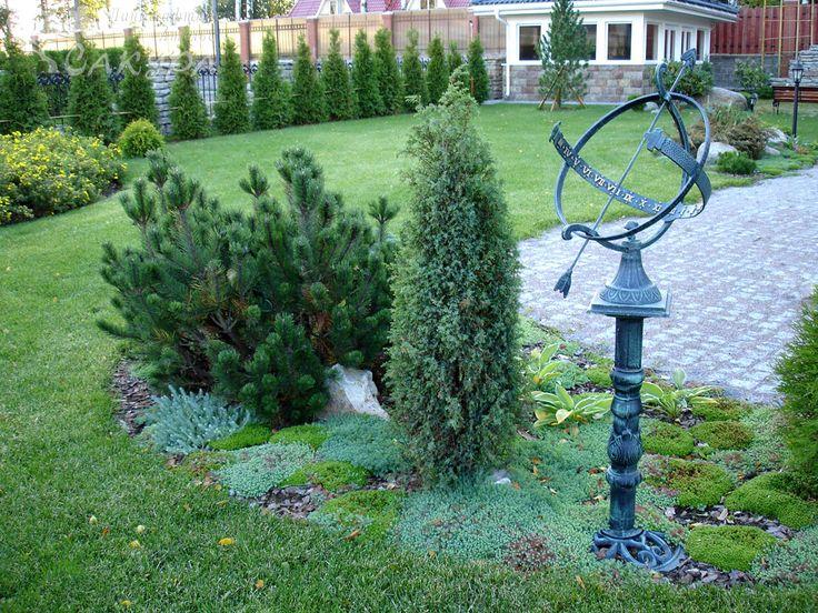 Композиция из растений с кованым элементом (солнечные часы)