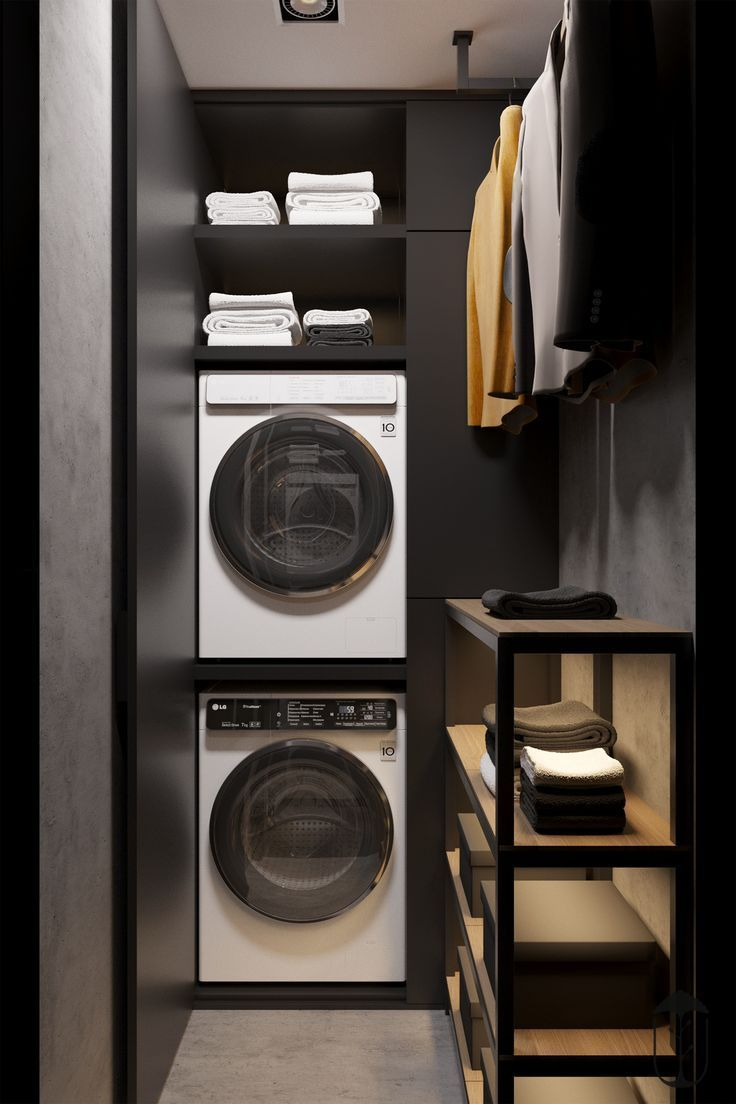 small space laundry room with dark walls and stack…