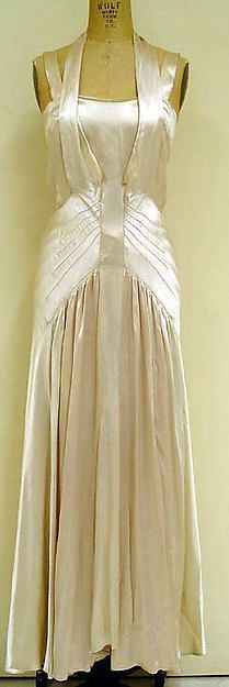 Evening dress by French designer, Bruyere (1928)  This rayon gown is a fitted sheath from the bodice down over the hips.  The bias-cut skirt is gathered around the hips.  The straps run up over the bustline and ties at the back of the neck.