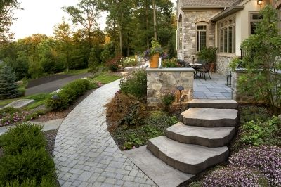 This outdoor living space includes a walkway featuring Techo Bloc Elena Pavers and Techo Bloc Maya Steps to a front porch using Techo Bloc Aberdeen Slabs.