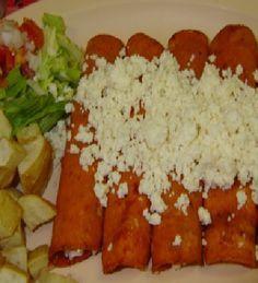 enchiladas rojas de pollo ( se remoja las tortillas en salsa de los siguientes chiles )chile ancho, mirasol y guajillo, rellenas de pollo , para decorar cebolla, ajo, crema y queso fresco.