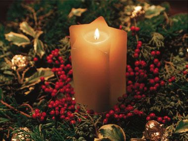 Natural elements, like evergreen branches, pinecones, and berries, make simple candles look festive. Display them together on a table or mantle. Just make sure to place candles in a protective holder, like a hurricane glass, so the branches or pine cones don't accidentally catch on fire.
