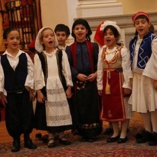 GREECE – The night before Christmas, children go from door to door offering good wishes for the season and singing kalanda or carols accompanied by the sounds of triangles. Gifts are given on Saint Basil's Day, the first day of January, and in place of a Christmas tree a shallow wooden bowl is placed in the home, holding a sprig of basil and a wooden cross