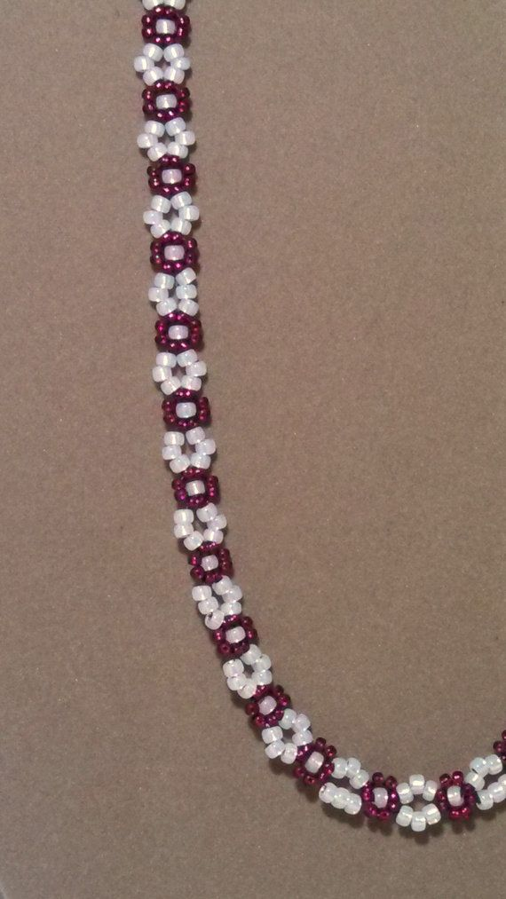 This cute necklace is woven together using the daisy chain weave. With cranberry and gilt-lined snow white seed beads. Has a silver toggle