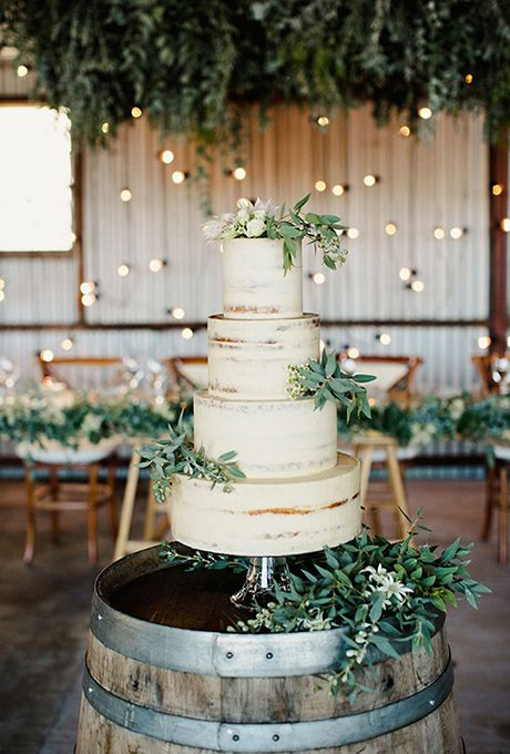 White Wedding Cake Decorated With Greenery. A thinly-frosted white wedding cake…