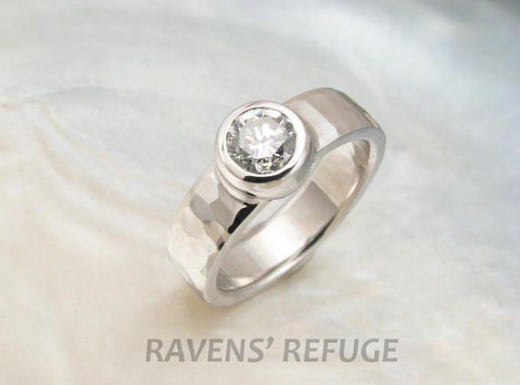 Cette magnifique bague sera faite sur commande et peut être personnalisée selon vos préférences. Comme sur la photo (et prix), la bague présente une magnifique.50 carats de diamants de couleur G et de pureté. Situé dans une lunette à la main--qui n'est pas coulé ou acheté préfabriqué et soudé sur une bande, comme de nombreuses bagues de fiançailles ces jours--, le diamant se trouve sur le dessus d'une bande de 5 mm x 2 mm en or blanc 14 k. Dan a martelé le groupe avec notre motif belle…