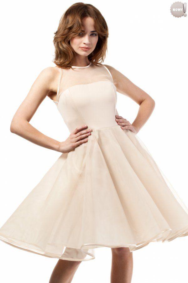 Beżowa, wieczorowa sukienka odcięta w pasie, góra dopasowana z tiulowym dekoltem wiązanym z tyłu aksamitną tasiemką, dół rozkloszowany, warstwowy z wierzchnią tiulową warstwą zakończoną atłasową lamówką.
