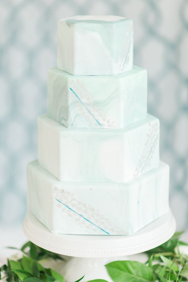 This hexagonal shaped light blue marble wedding cake stands tall on its own!