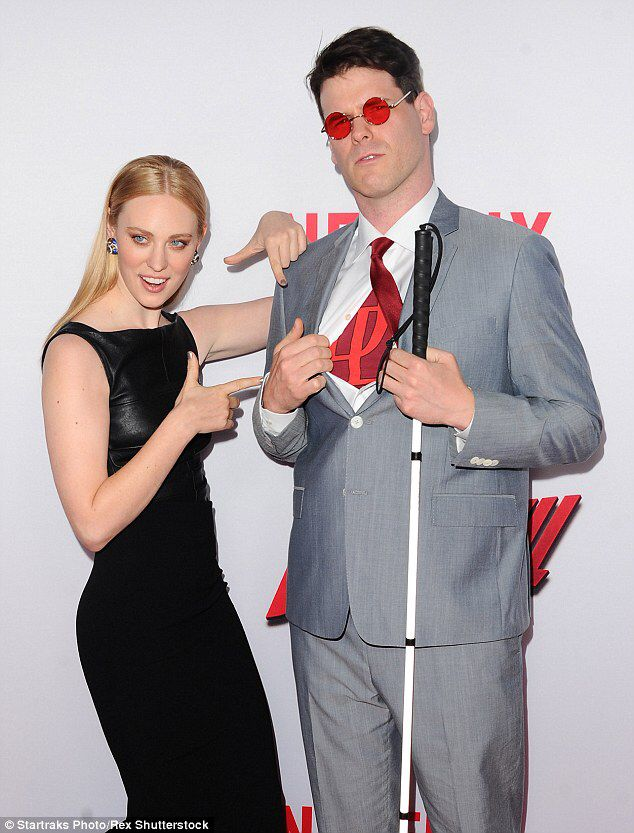 See the swag lady on the left? That Deborah Ann Woll, the amazing Karen Page in Daredevil. See the cool guy on the right? That's her husband, E. J.  He is a fan of Daredevil and has a degenerative disease that causes blindness. It was a very important role for Deborah because of having a blind superhero on TV.  Her husband dressed as Matt Murdock for the premiere red carpet, with the Daredevil symbol beneath his shirt.  What an amazing story :)) #RepresentationMatters !!