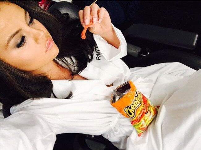Selena Gomez with cheetos... Oops, she won't be having them for some time now...