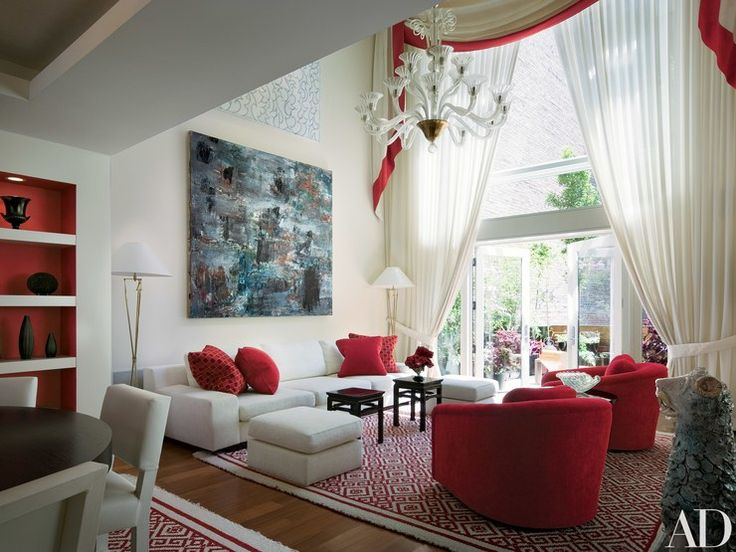 """I wanted to give a look of glamour and warmth to an austere building,"" interior designer Thomas Britt says of a Tribeca structure he converted into a home for an international couple. For the double-height living room windows, he hung elegant red-trimmed draperies. Above a painting by Louise Fishman is a work by Stan Gregory. Newel chandelier. Red coral, porcelain lion and pair of lamps, Bernd Goeckler Antiques. Jim Thompson drapery silk, with Clarence House red trim. Glant red chair"