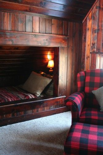A built-in bed in a wood-paneled room. Looks like a southwestern print blanket on the bed and a cozy buffalo plaid armchair with ottoman