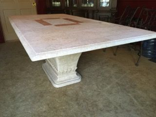 OUTDOOR/INDOOR TRAVERTINE STONE TOP TUSCANY DINING TABLE WITH PEDESTAL BASE WITH RAISED LEAVES. MEASURES 7 FEET LONG BY 42 INCHES WIDE AND 30 INCHES HIGH. BEAUTIFUL TABLE IN GENTLY USED CONDITION BUT PLEASE NOTE THERE ARE A FEW INK STAINS ON THE TABLE. WHILE THIS LOT IS FOR THE TABLE ONLY, IT DOES COORDINATE WELL WITH THE WOODARD LANDGRAVE CHAIRS IN LOT 10186.