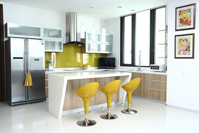 A splash of yellow plays up the white walls and cabinets with light wood finish. The breakfast nook is a favorite spot not just for the family, but for guests as well. Medium density fiberboards are used for the kitchen cabinets, together with glass and aluminum frames for a modern touch.��