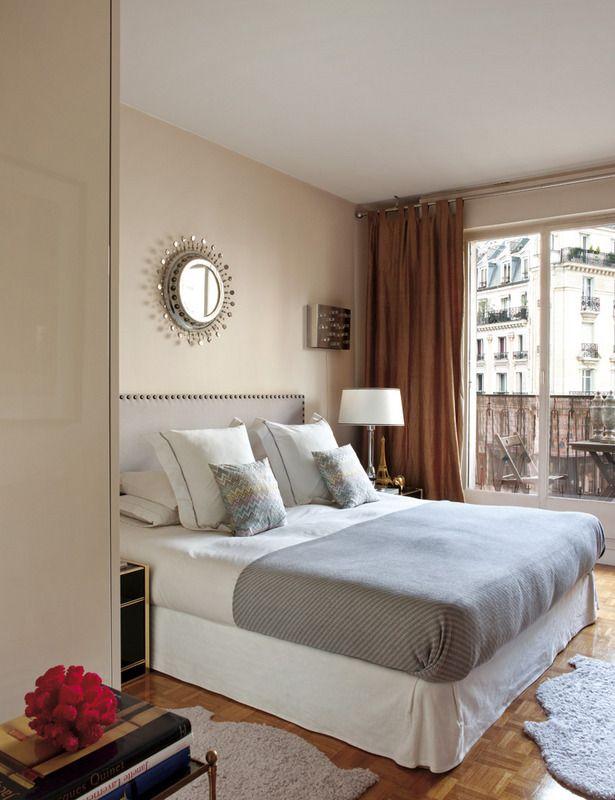 Con alegres vistas a la rue de Passy, el dormitorio de Julia y Horacio está vestido en tonos cálidos y neutros. Ellos diseñaron el cabecero de una cama vestida con cuadrantes de Zara Home y cojines de Missoni. Espejo cerámico de Georges Pelletier y lámpara de Jumo, años 50.