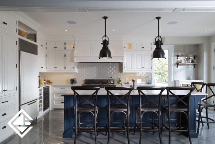 Gorgeous traditional kitchen with large quartz countertops and custom made white cabinets offsetting the navy blue island cabinets.