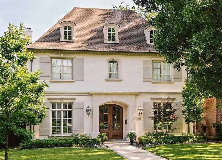French home features exterior clad in white brick accented with light gray shutters.