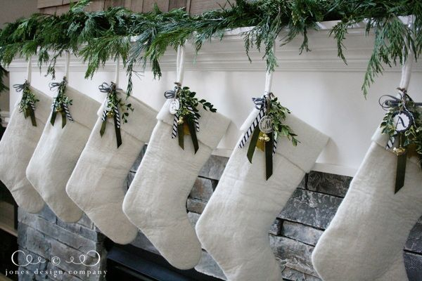 embellishing simple white stockings: Emily at Jones Designs takes West Elm stockings and jazzes them up with a hot glue gun, some greenery and a few loops of charming ribbon @Tara Harmon Harmon Taggart