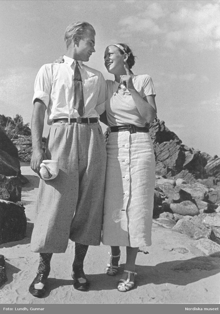 1936. Sommar vid stranden, Sandkaas på Bornholm. Man och kvinna i ledig fritidsklädsel står sida vid sida och håller om varandra, ser varandra djupt i ögonen och ler. Fotograf: Gunnar Lundh