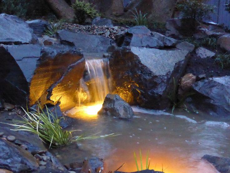 Waterfall lit up at night.