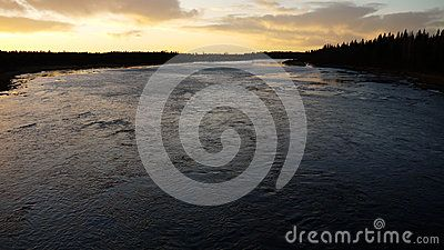 Panoramic view of the sunset over a wide arctic river in winter.