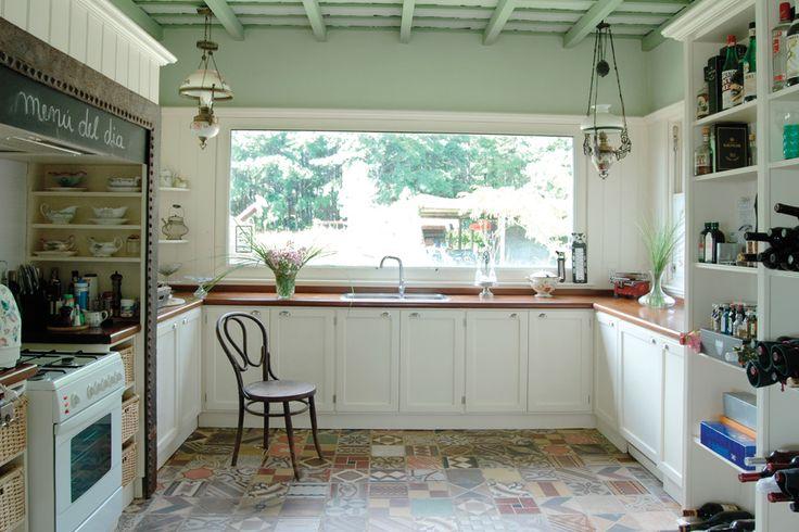 Pisos de mosaico, muebles antiguos recuperados y el techo revestido en madera pintada otorgan calidez a esta cocina de dimensiones generosas.  /Archivo LIVING