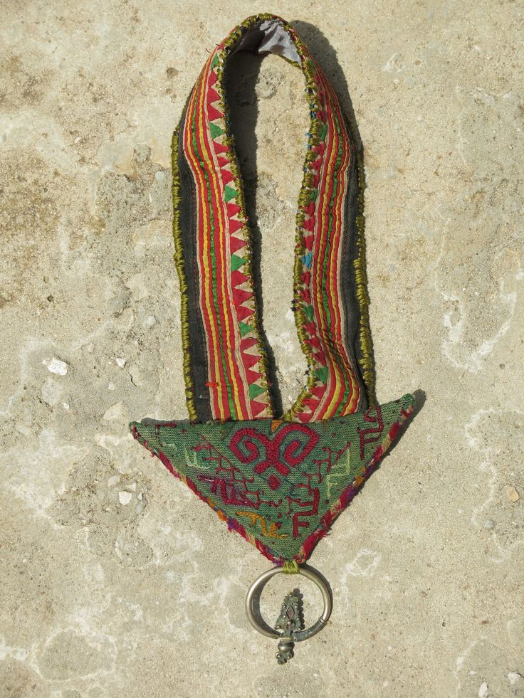 ETHNIC TREE: Ethnic necklace whose base is made of a vintage piece of applique, coming from a woman's belt from the Hmong tribe in the Hoa Binh province (Vietnam). The central triangular piece is an Afghani amulet, where people traditionally hid scriptures for protection. The sterling silver earring (925k) is Hmong and also comes from Vietnam. This necklace is entirely handmade and a unique piece. www.ethnictree.com
